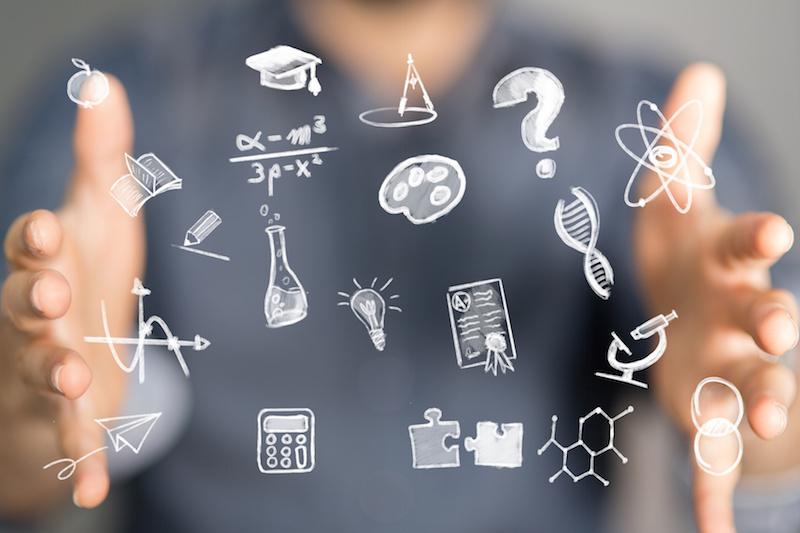 Grafika przedstawiająca symbole związane z edukacja na ekranie, w tle dłonie