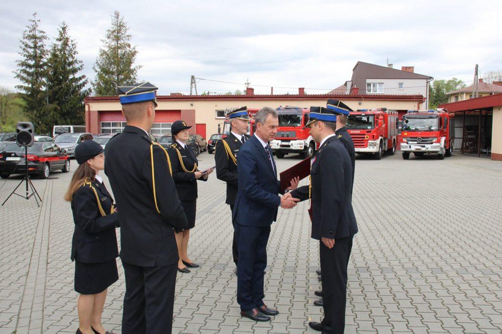Starosta Limanowski Mieczysław Uryga przekazuje gratulacje awansowanemu strażakowi. Wręcza mu list gratulacyjny i ściskska dłoń.