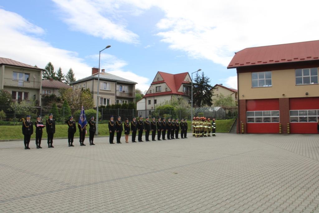 Widok na plac przed Komeda Powiatową Straży Pożarnej w Limanowej, na którym stoją ustawieni w rzedzie strażacy.