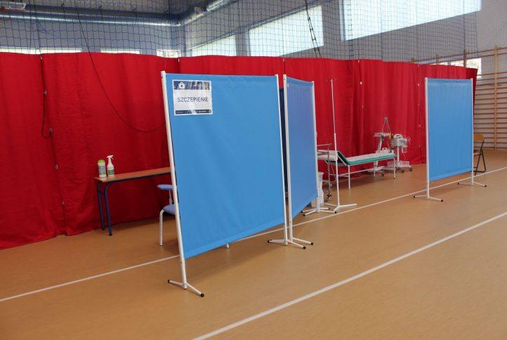 Zdjęcie części hali sportowej przygotowanej do wyknywania szczepień. Czerwone kotary i niebieskie parawany . Na zdjciu widoczne jest również łóżko dla pacjentów