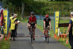 dwóch rowerzystów przejeżdża linię mety