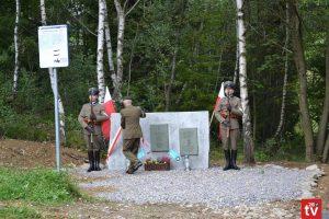 Widok na pułkownika, który uroczyyście odsłania obelsik z trzema tablicami pamiąrtkowymi.