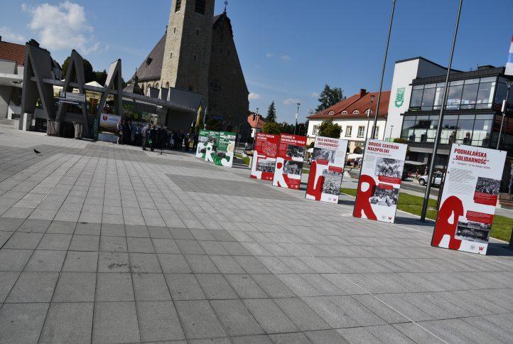 """Widok na wystawę """"Tu rodziła się solidarność"""" na rynku w Limanowej. W tle budynek PCIT <a href="""