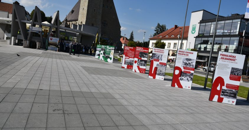 """Widok na wystawę """"Tu rodziła się solidarność"""" na rynku w Limanowej. W tle budynek PCIT Limanowa oraz Bazylika MBB"""