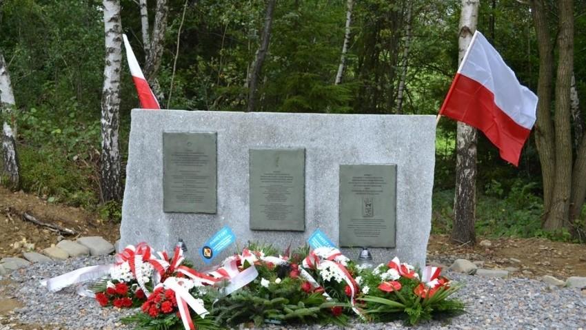 Zdjęcie przedstawia obelisk z trzema talicami pamiątkowymi. Pod obeliskiem są złożone patriotyczne wiązanki, nad obliskiem powiewają dwie polskie flagi.