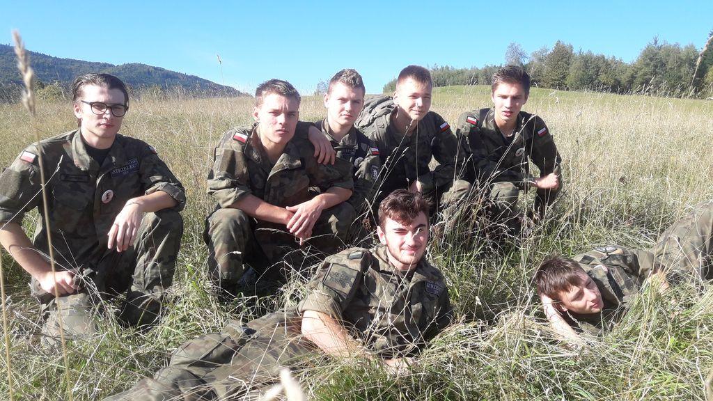 Sześciu chłopców w mudurach wojskowych na trawie podczas rajdu.