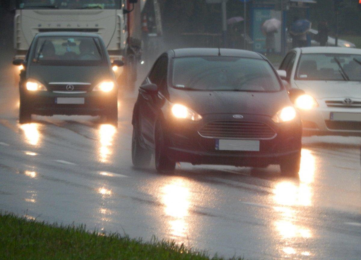 Zdlecie przedstawiajace samochdy na drodze z właczonymi światłamiw deszczowej pogodzie