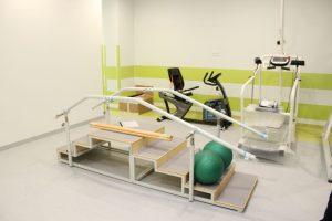 wnetrze sali rehabilitacyjnej, na zdjęciu widoczne trzy przyrządy do ćwiczeń