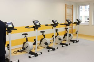zdjecie przedstawiajace sale do rehabilitacji, przy ścianie ustawione cztery rowery treningowe