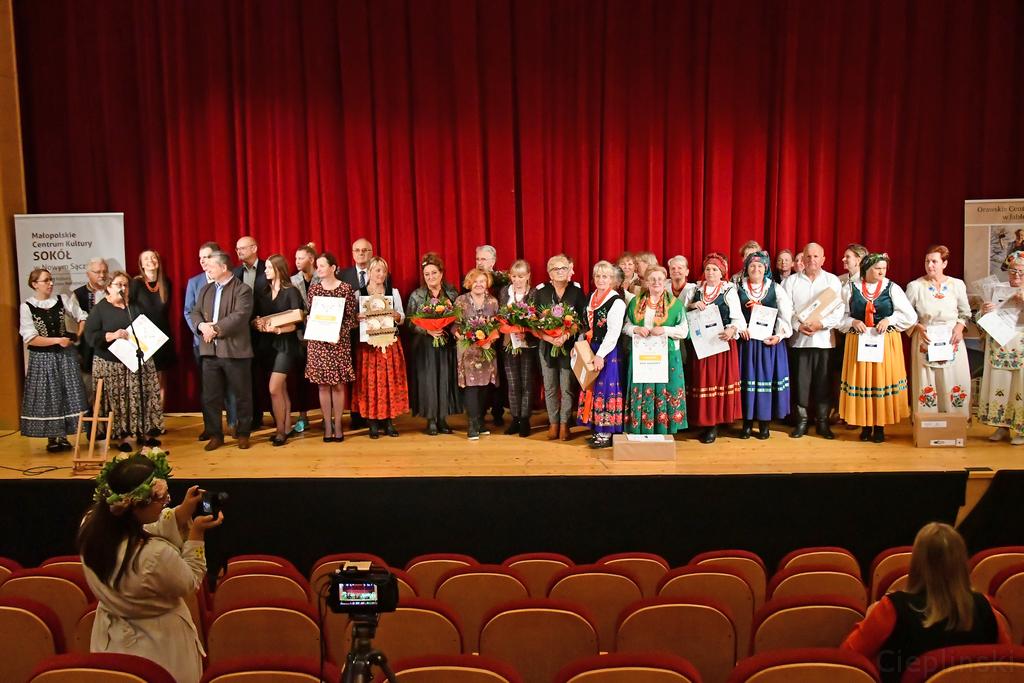 Zdjecie przedstawiajace grupę laureatów 11 małopolskiego Przegladu Dorobku kulinarnego i Artystycznego Kół Gospodyń Wiejskich w Jabłonce pozujących na scenie do wspólnego zdjęcia