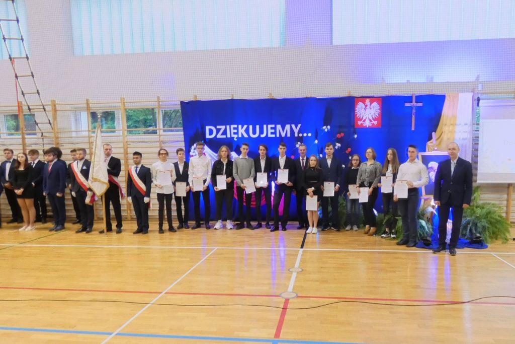 Zdjęcie przedstawia liczną grupę uczniów wyróżnionych stypendium przyznanym przez Starostę Limanowskiego (stoi pośrodku), dyrektora Wydziału Edukacji i Sportu Starostwa Powiatowego w Limanowej - Artura Krzaka (stoi w rzędzie pierwszy po prawej) oraz poczty sztandarowe, zgromadzonych w sali gimnastycznej